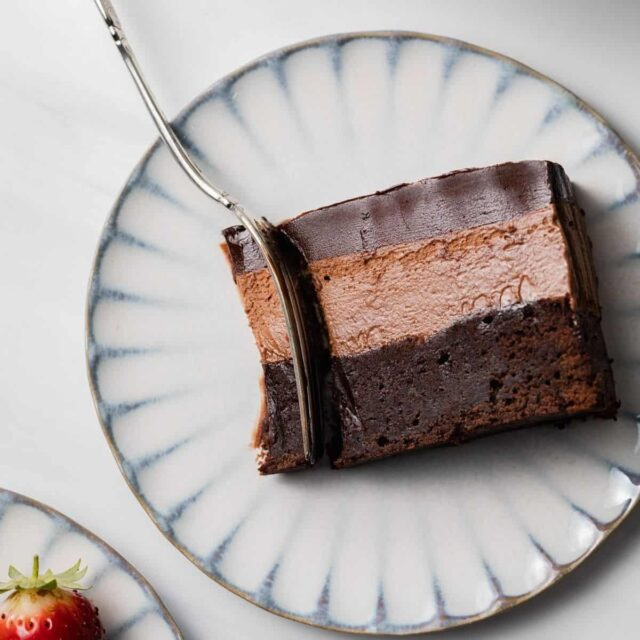 Slice of triple chocolate mousse cake on plate with fork taking a bite out.