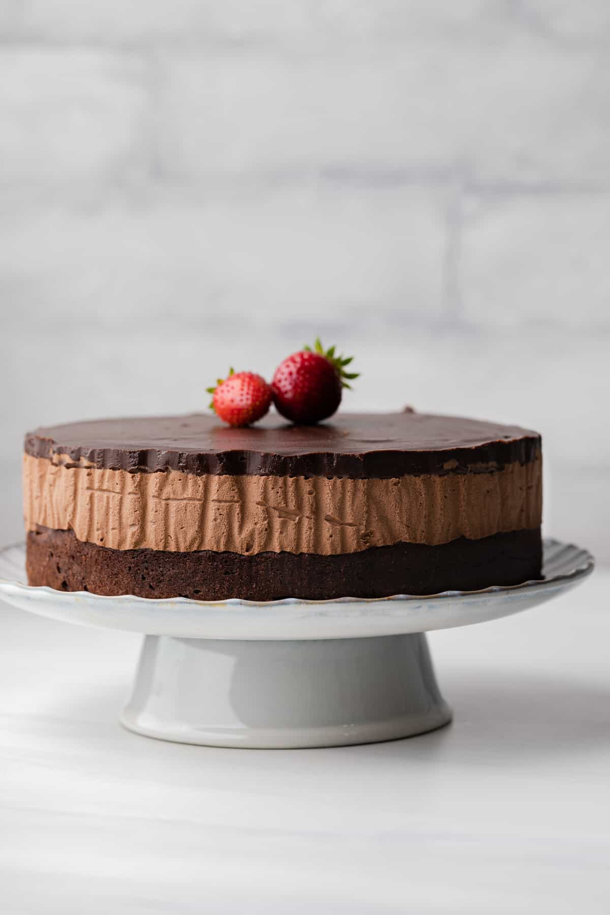 Triple chocolate mousse cake on a white cake stand with large strawberries stacked on top of the cake.
