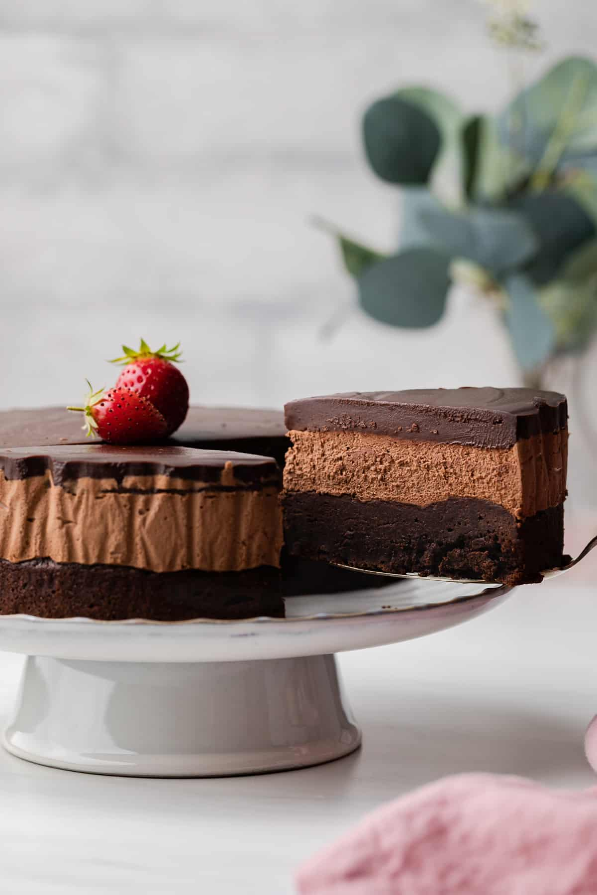 A Close Up View Of Triple Chocolate Mousse Cake Sitting On White Plate With