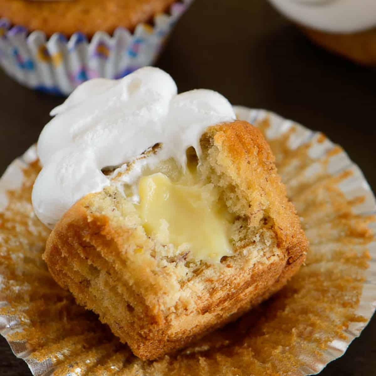 A banana pudding cupcake with a bite out so the filling inside is visible.