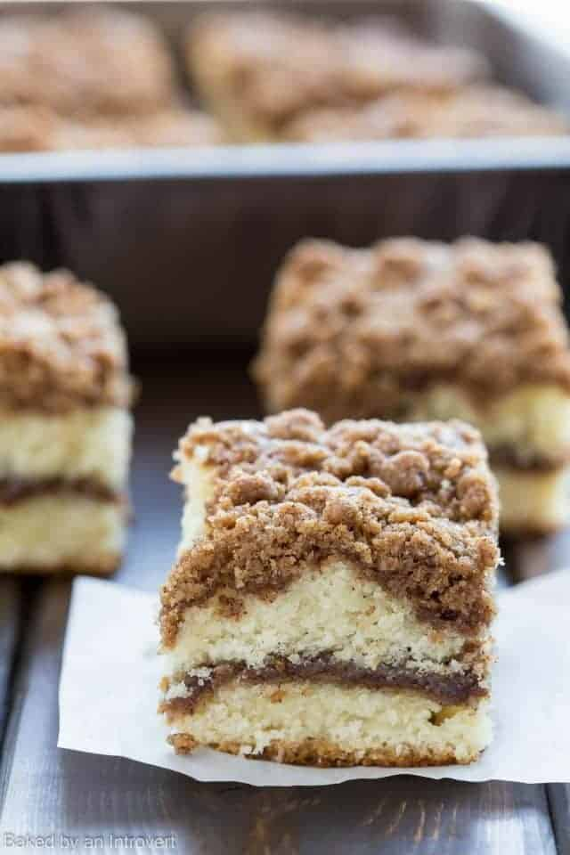 A slice of coffee cake with a ribbon of cinnamon in the center and topped with crunchy cinnamon streusel on a piece of white parchment paper.