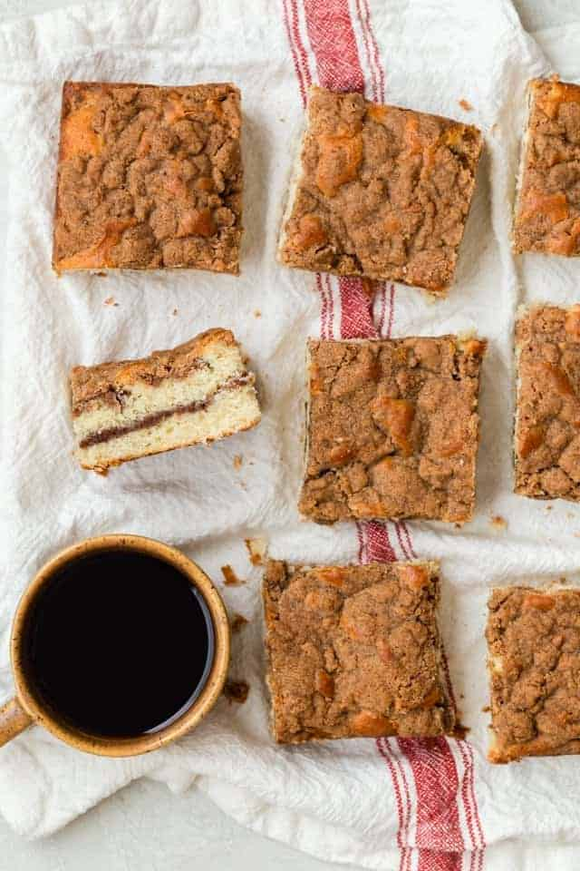 Cinnamon streusel coffee cake sliced on a white towel.