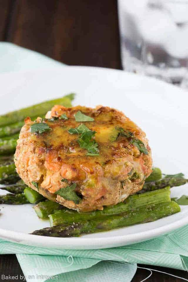 Oven baked salmon patty on top of sliced asparagus on a white plate.