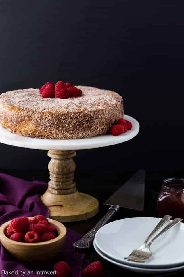 Raspberry Jelly Donut Coffee Cake on a marble cake stand with a stack of white plates and a bowl of raspberries.