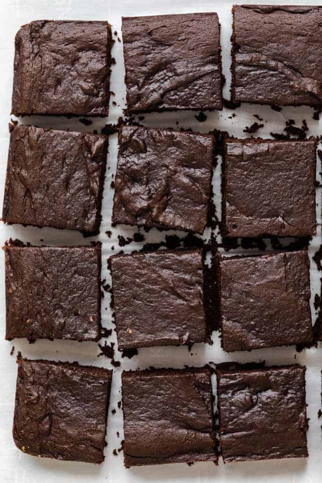 Vegan brownies on a white board, loaded with chocolate