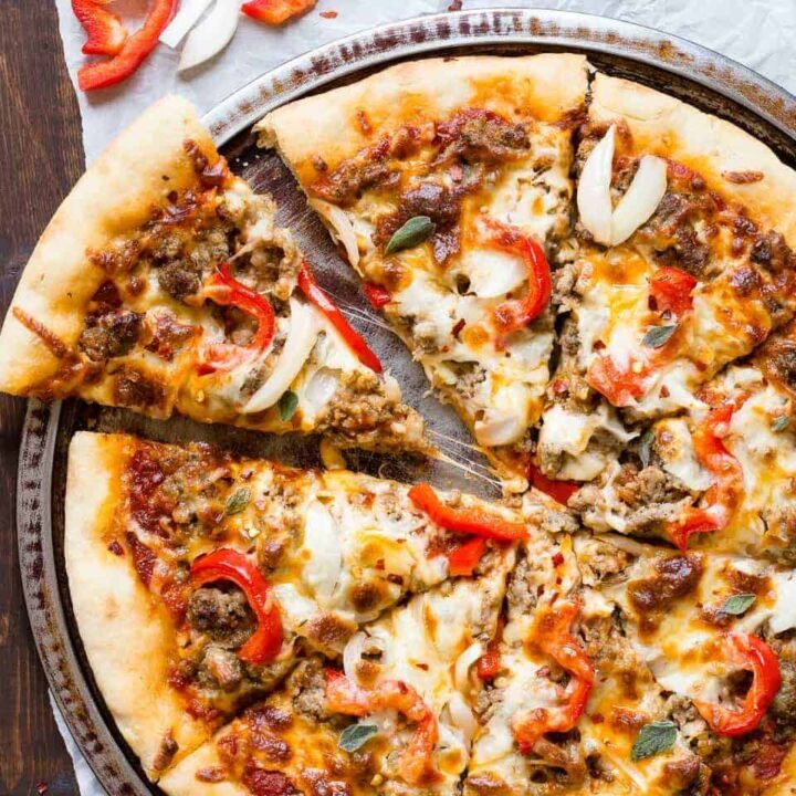 spicy sausage pizza cut into 8 slices on a round pan