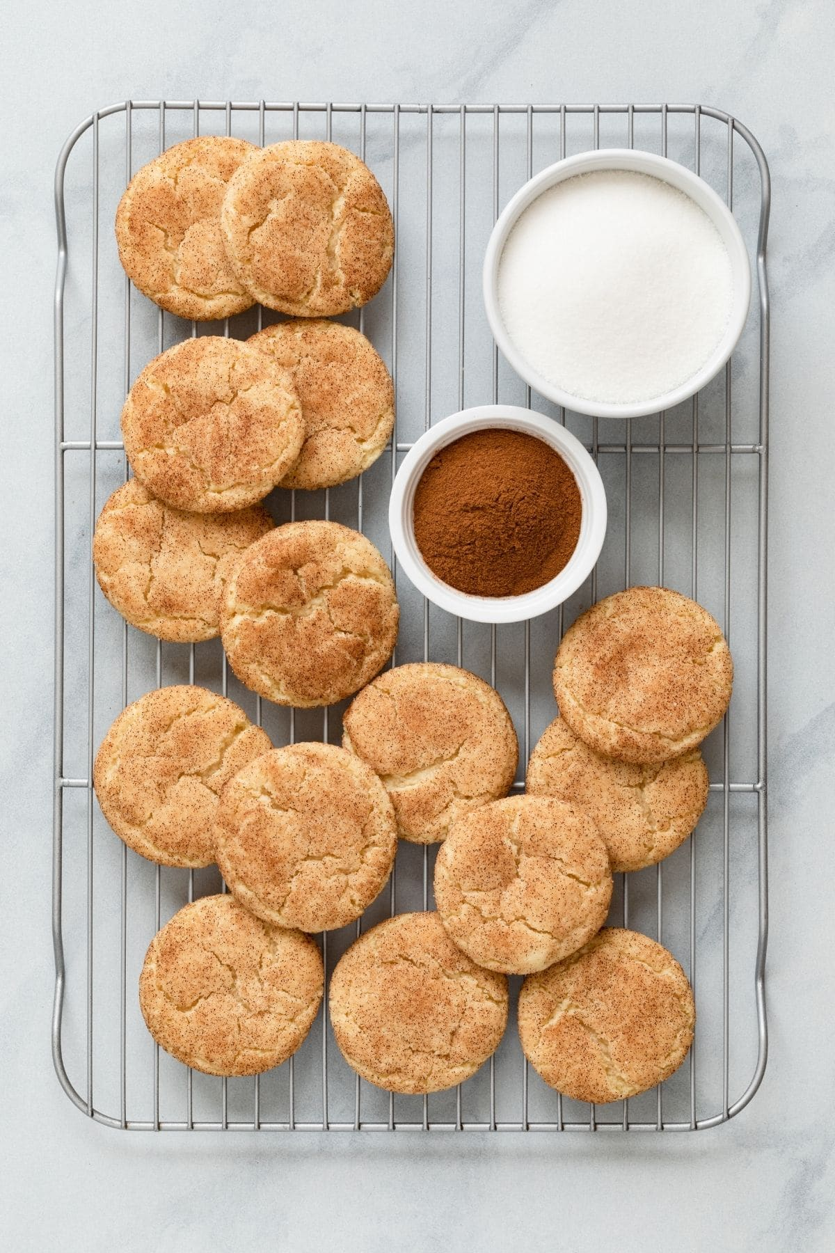 snickerdoodle cookies on wire rack with bowls of cinnamon and sugar