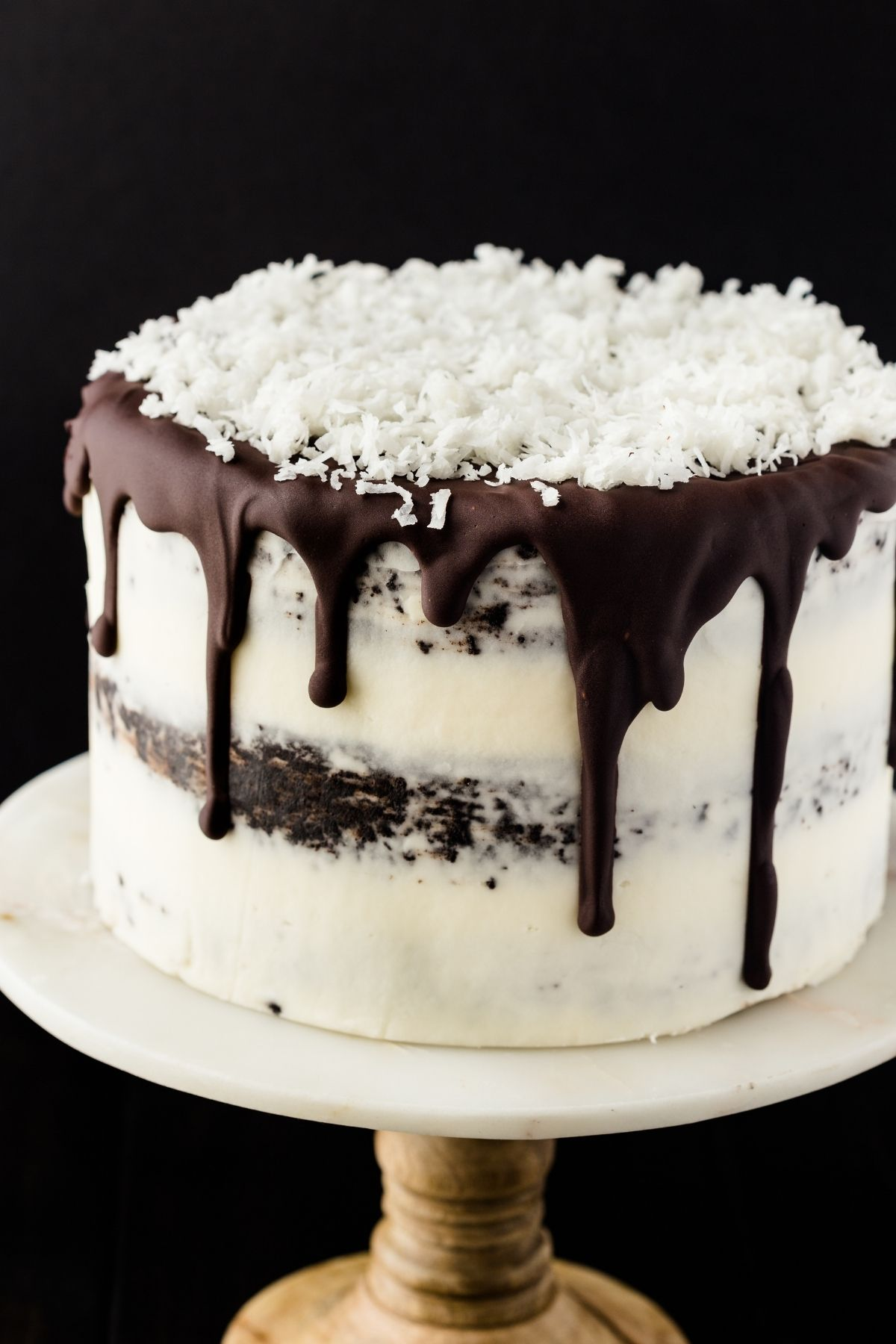 Chocolate coconut cake with dripping ganache and coconut flakes on top sitting on a cake stand.
