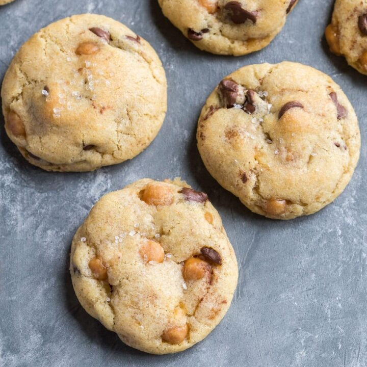 Overhead view of Soft and chewy Chocolate Chip Salted Caramel Cookies on a grayish blue background.