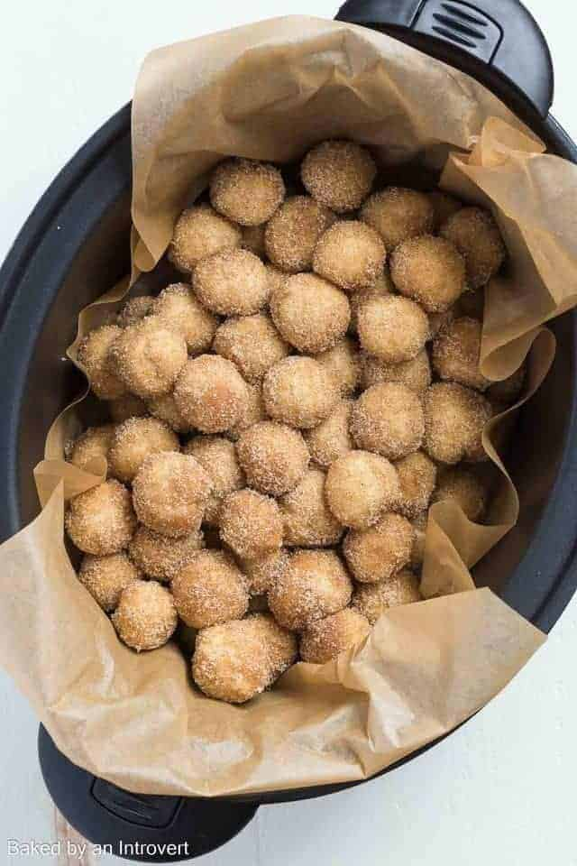 Overhead view of raw slow cooker monkey bread dough balls in a slow cooker lined with brown parchment paper.