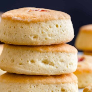 side view of three buttery jam biscuits stacked on one another
