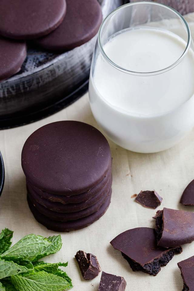 High angle view of a stack of thin mints next to a glass of milk.