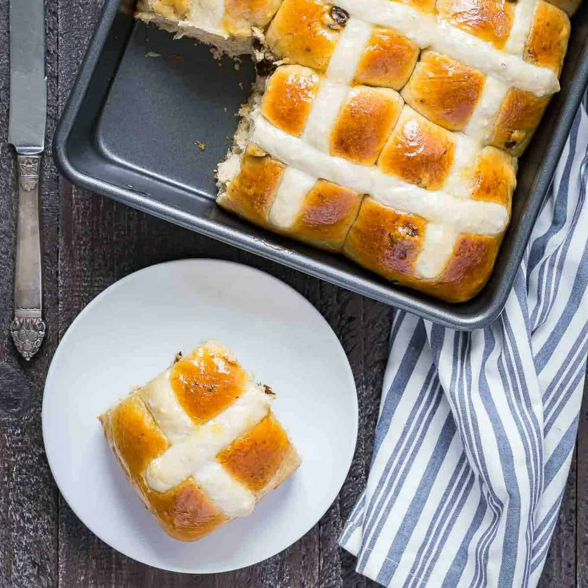 pan of Hot Cross Buns with one taken out and placed on a plate