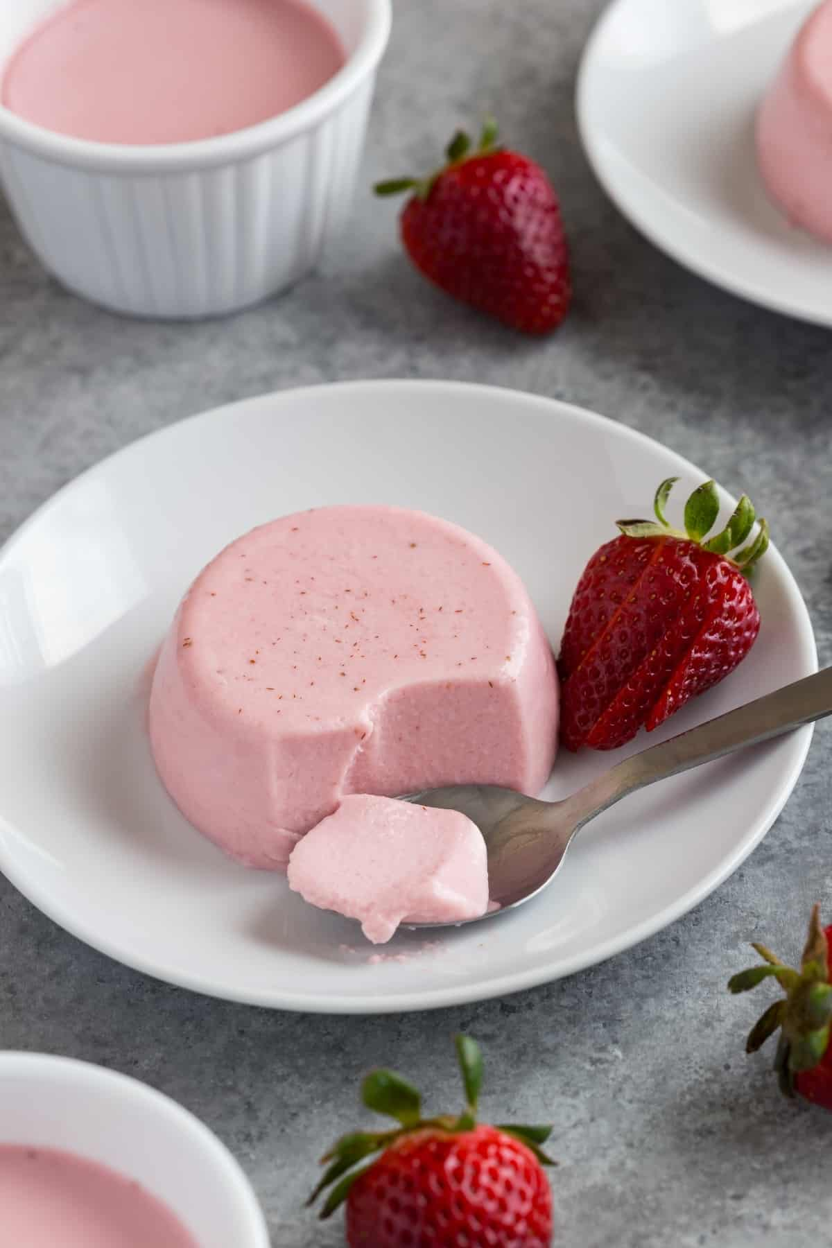 Creamy strawberry panna cotta on a white plate with a spoon taking a bite out.