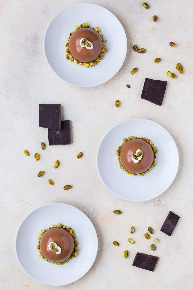 Overhead view of three chocolate pistachio domes on white plates.
