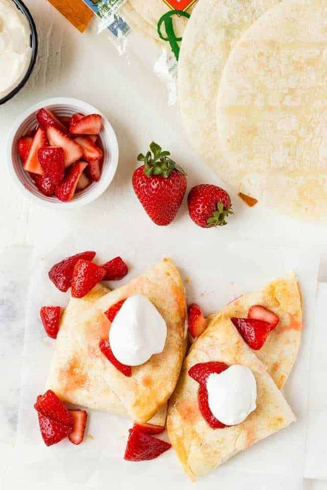 Overhead view of fresh strawberries and cream cheese stuffed inside flour tortillas,