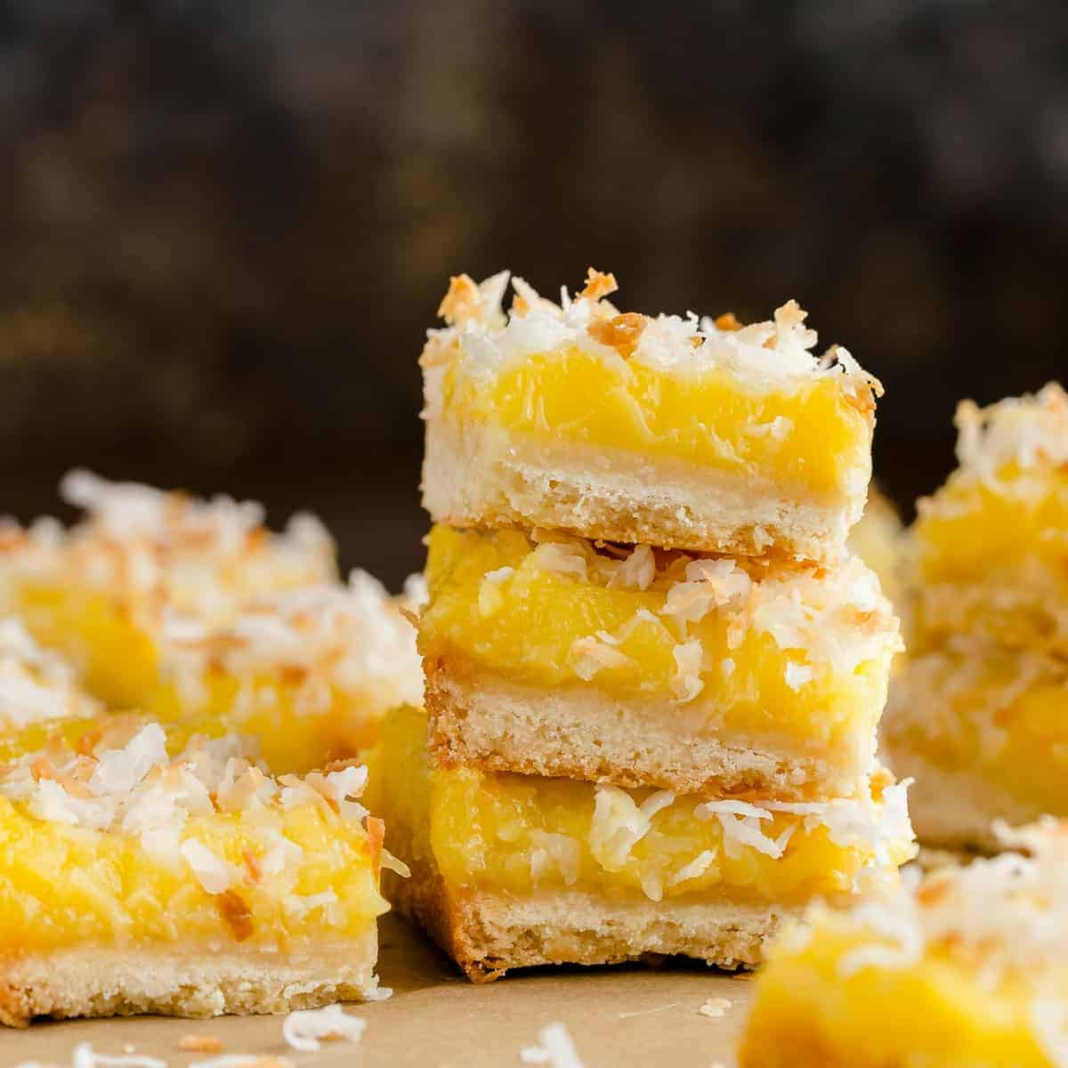 Coconut lemon bars stacked on a table.
