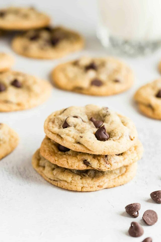 Three Chewy Chocolate Chip Cookies stacked on a white background.