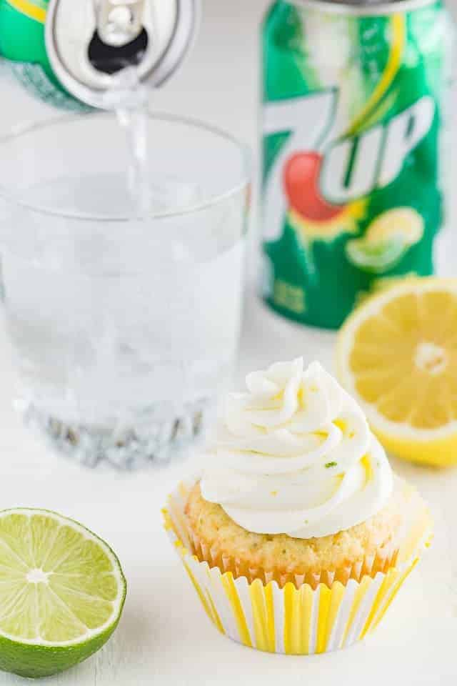 Angled view of lemon lime cupcakes with a can of 7up being poured into a glass.