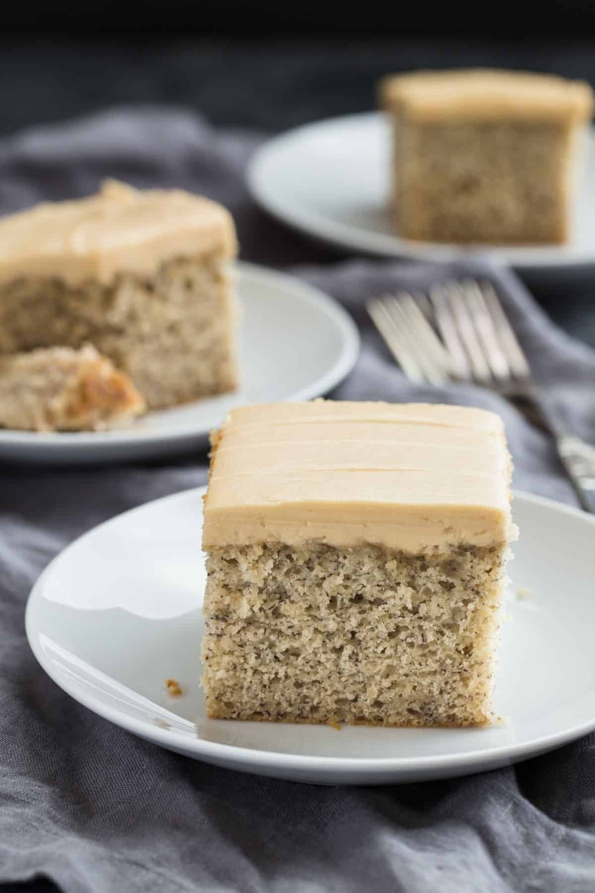 A slice of Easy Banana Cake recipe topped with luscious brown sugar frosting on a white plate.