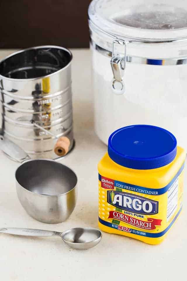 A jar of cornstarch, container of flour, measuring spoon, measuring cup, and sifter on a counter.