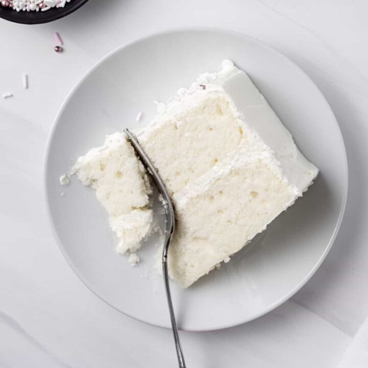 A slice of moist white cake with buttercream frosting on a plate, with a fork cutting off a bite