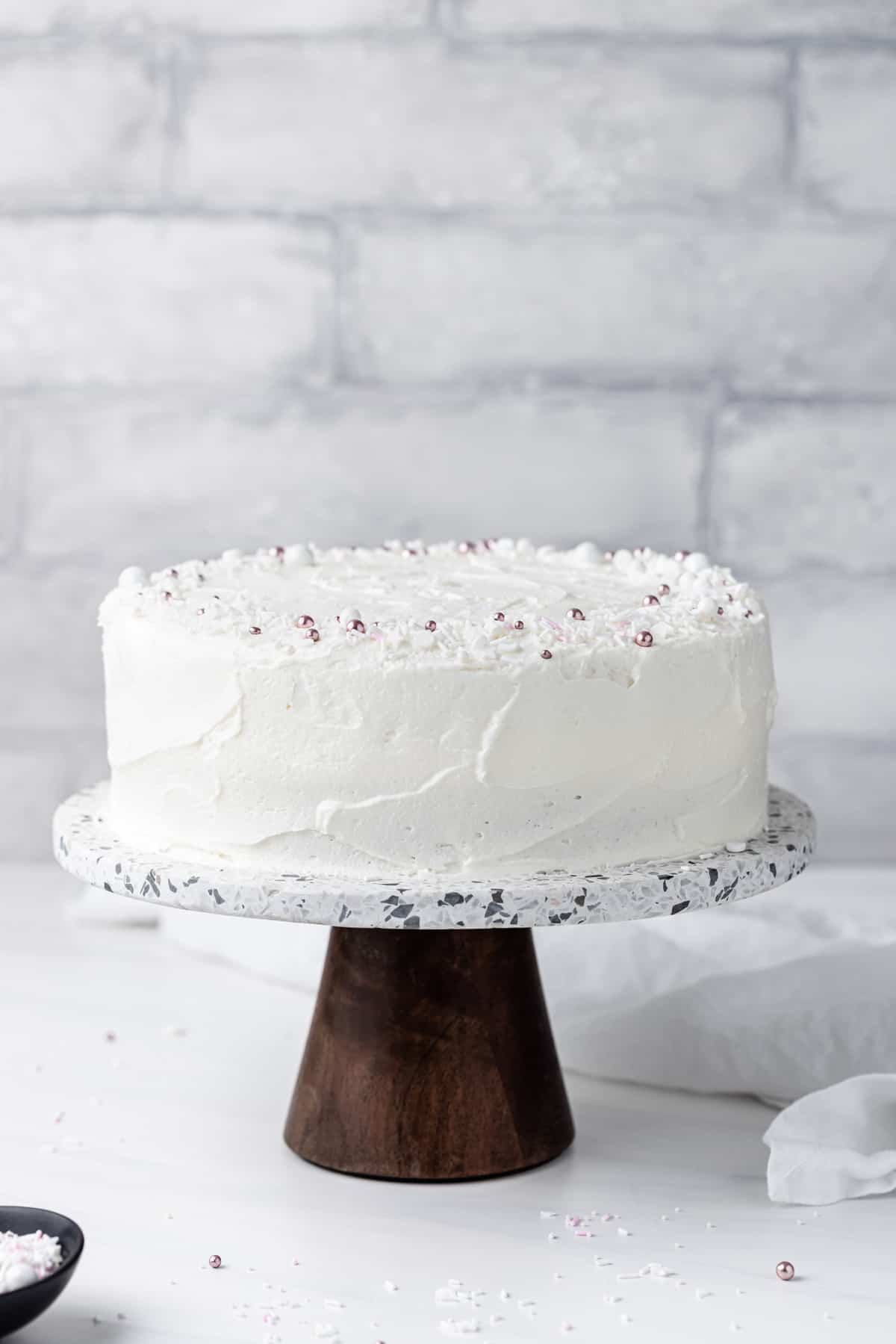 Moist white cake recipe with white frosting on a stone grey cake stand with a wooden base.
