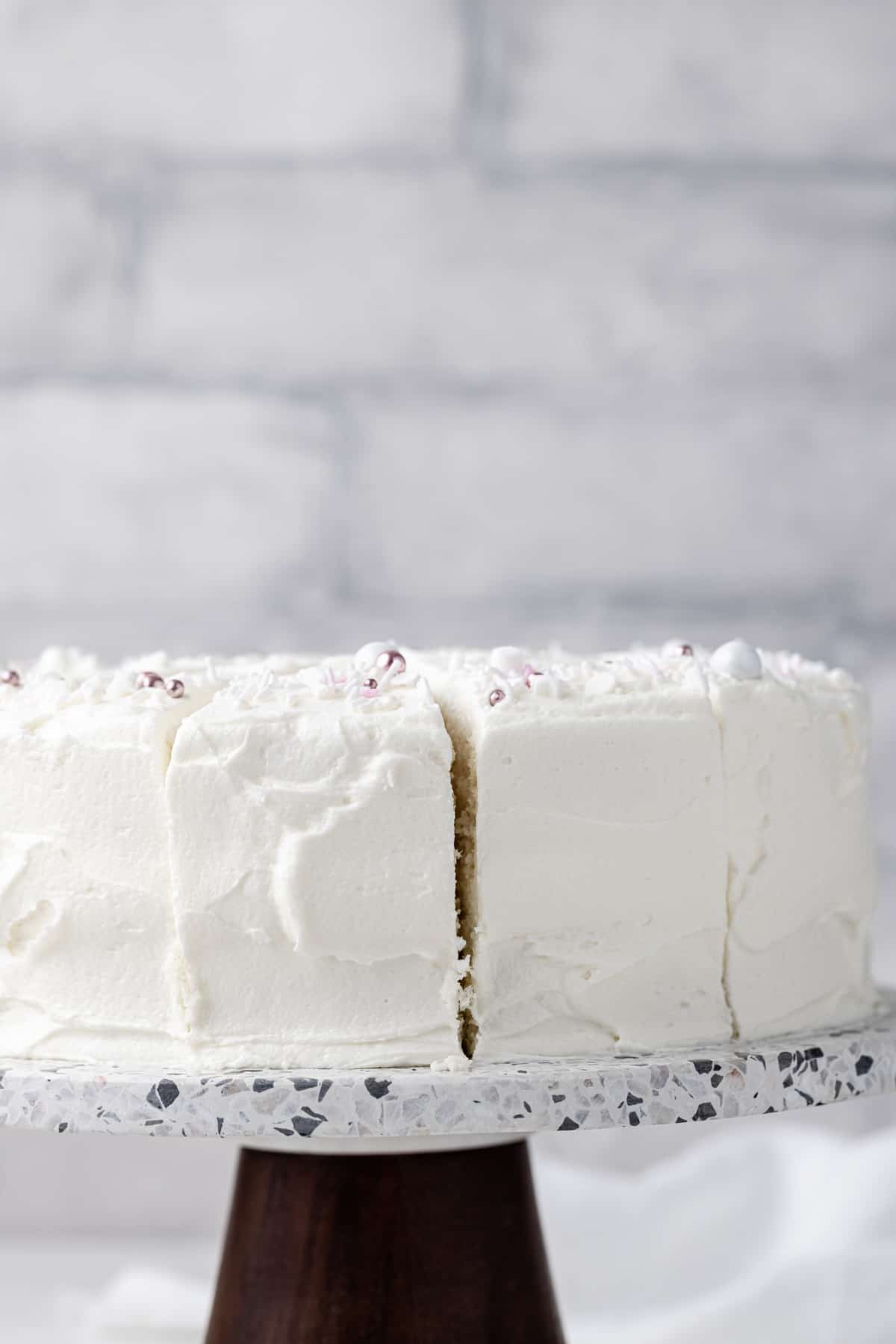 Close up view of a homemade white cake on a grey stone cake plate with a brown base.