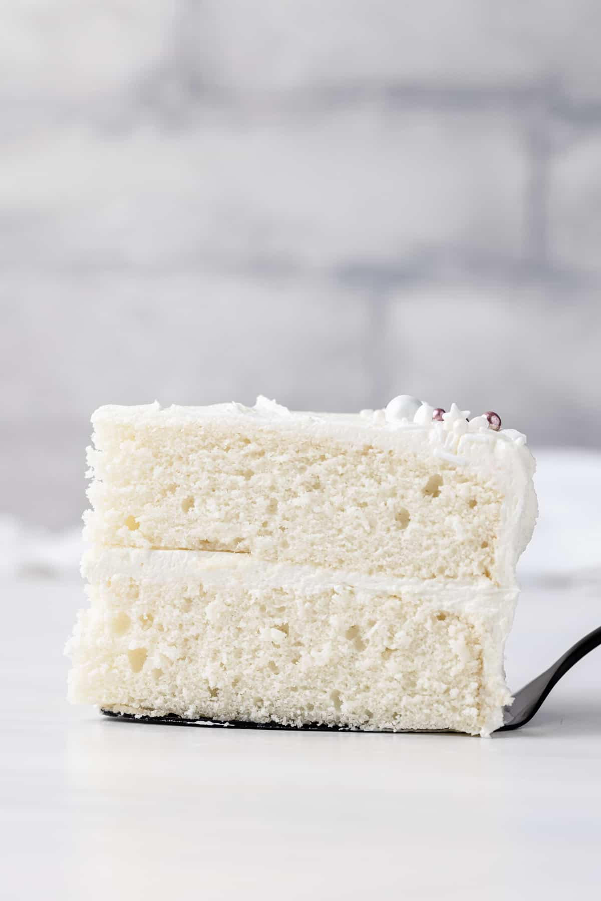 The best white cake on a grey slate cake stand with a slice of cake being taken out.