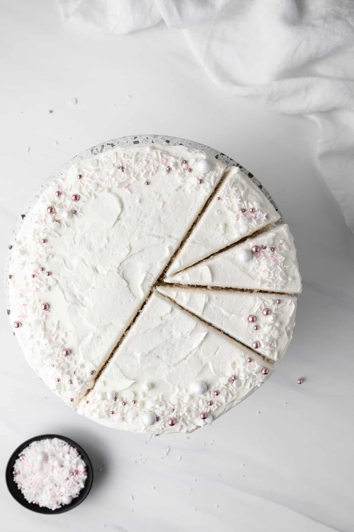 Frosted white cake, half cut into slices