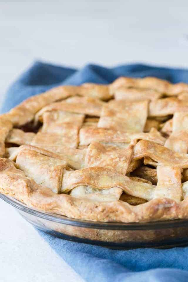 A lattice top apple pie in a glass pie dish sitting on a blue napkin.