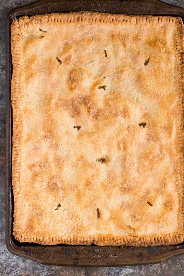 An apple slab pie baked to golden perfection in a large baking sheet.