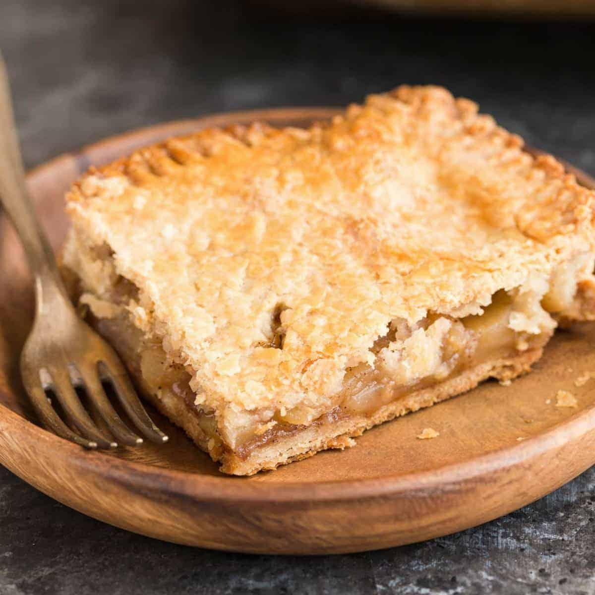 A square slice of apple slab pie on a wooden plate with a fork next to it.