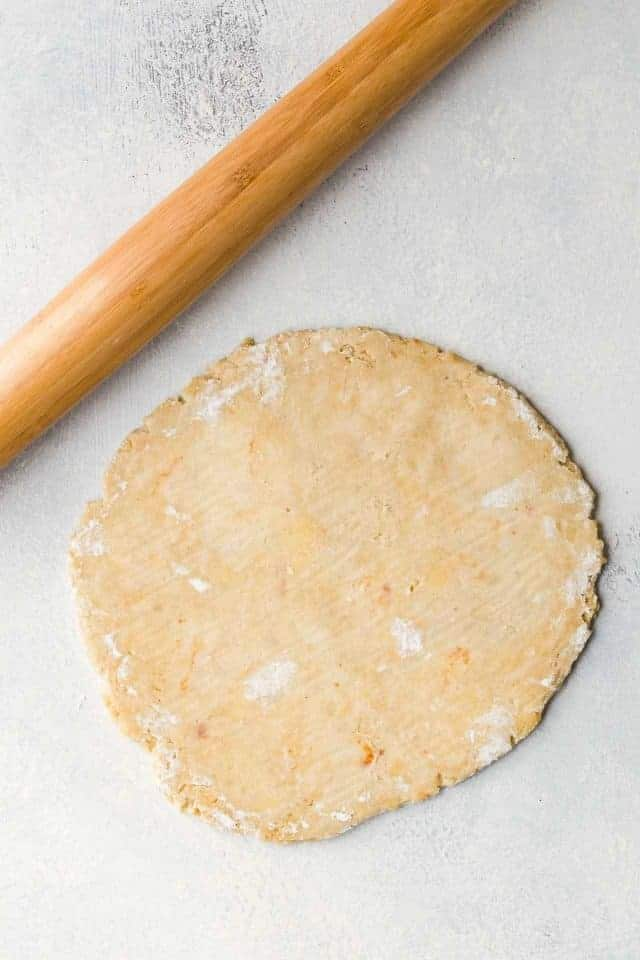 A disc of brown butter pie crust rolled out onto a white counter top with a wooden rolling pin sitting next to it.
