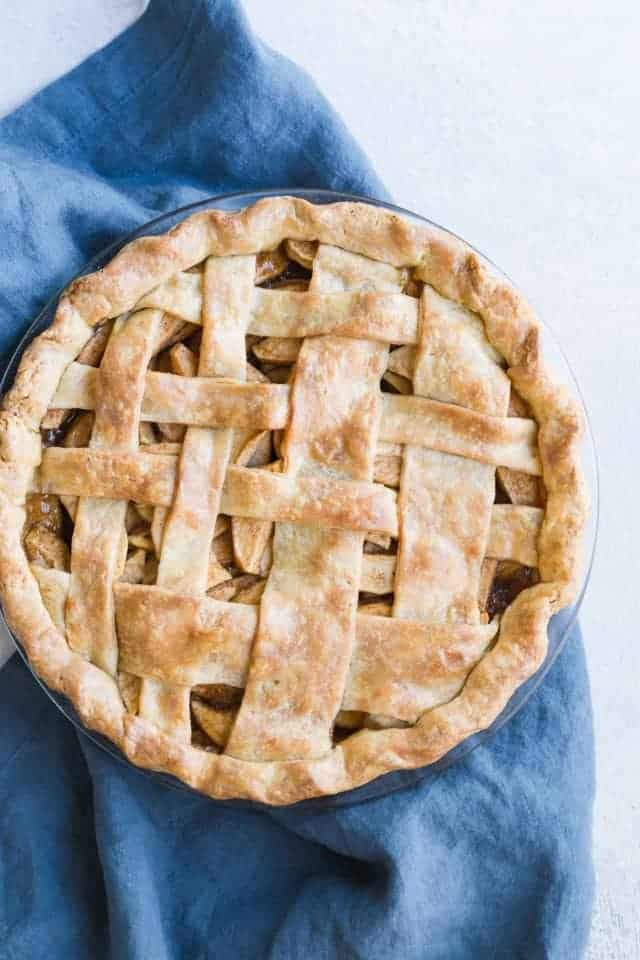 Gorgeous overhead view of a baked apple pie with brown butter crust sitting on a dark blue napkin.