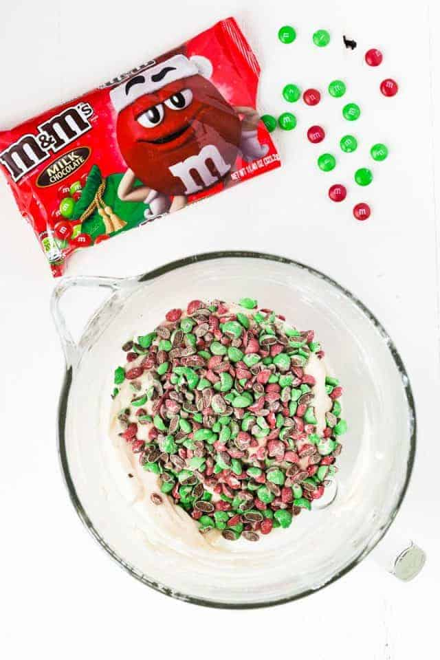 Chopped M&M'S on top of cupcake batter in a glass bowl.