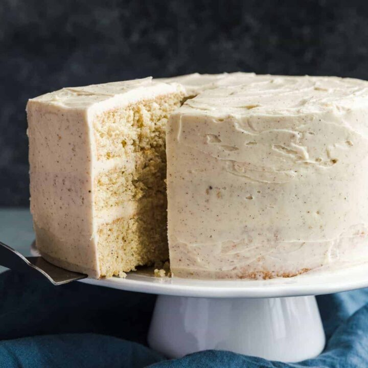 Eggnog cake on a white cake stand with a slice being taken out.