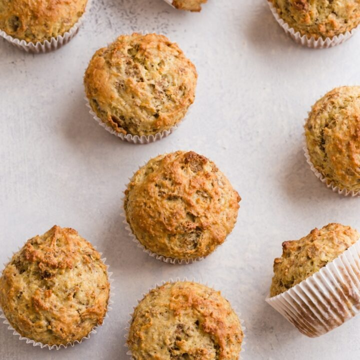 Banana Bran Muffins scattered on a white table top.