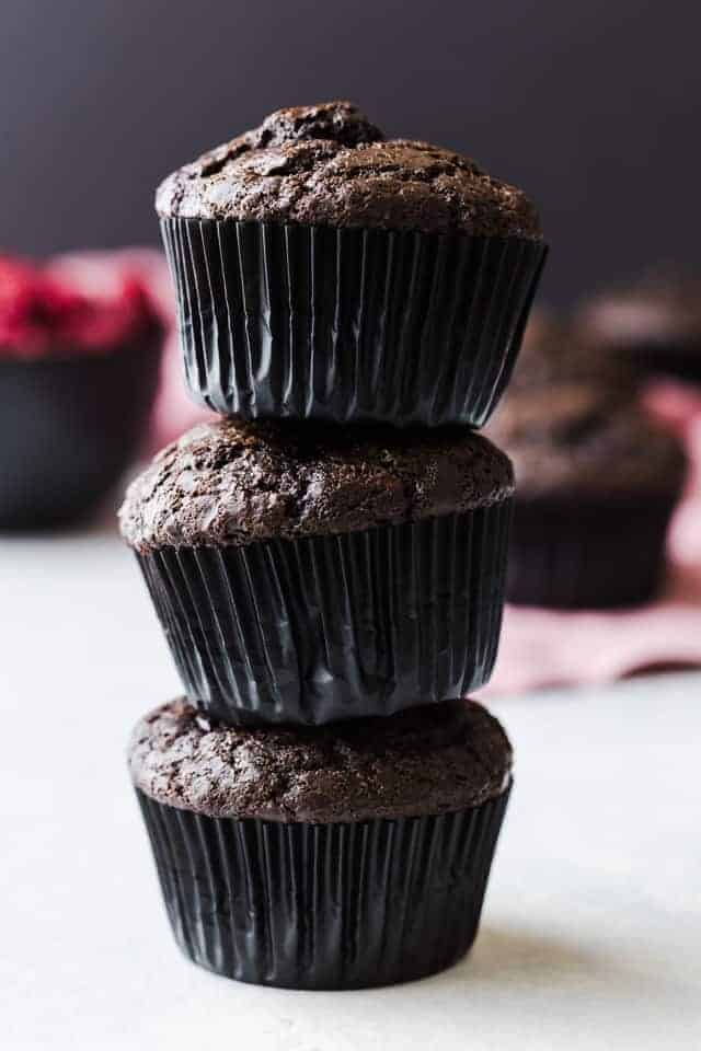 Three double chocolate muffins with raspberries stacked on a white tabletop.