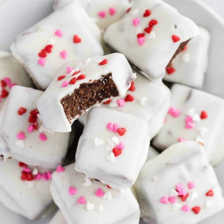 Mexican hot chocolate fudge coated in white chocolate stacked on a white plate.