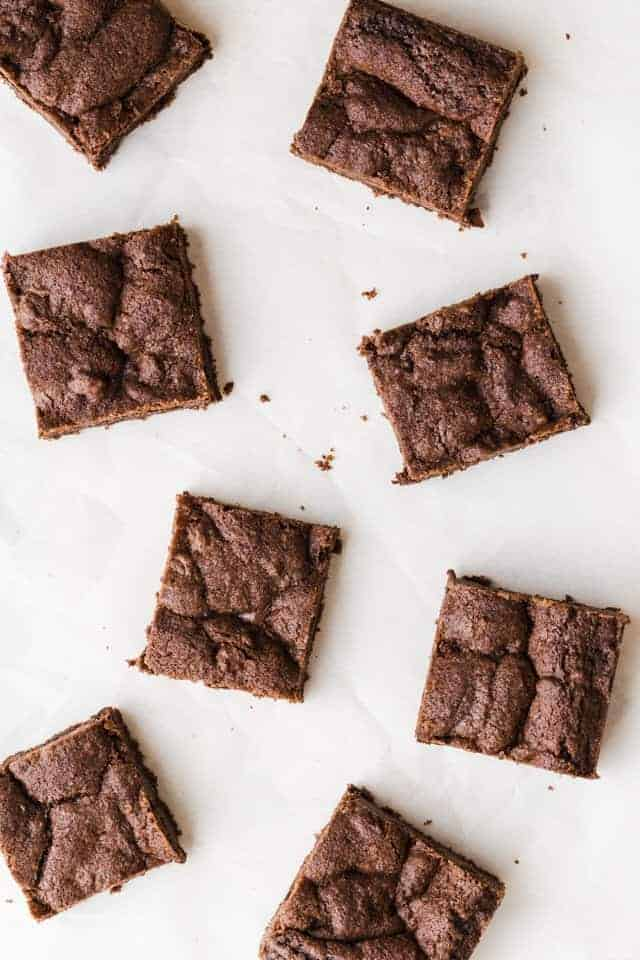 Chocolate nutella cookie bars scattered on white parchment paper.