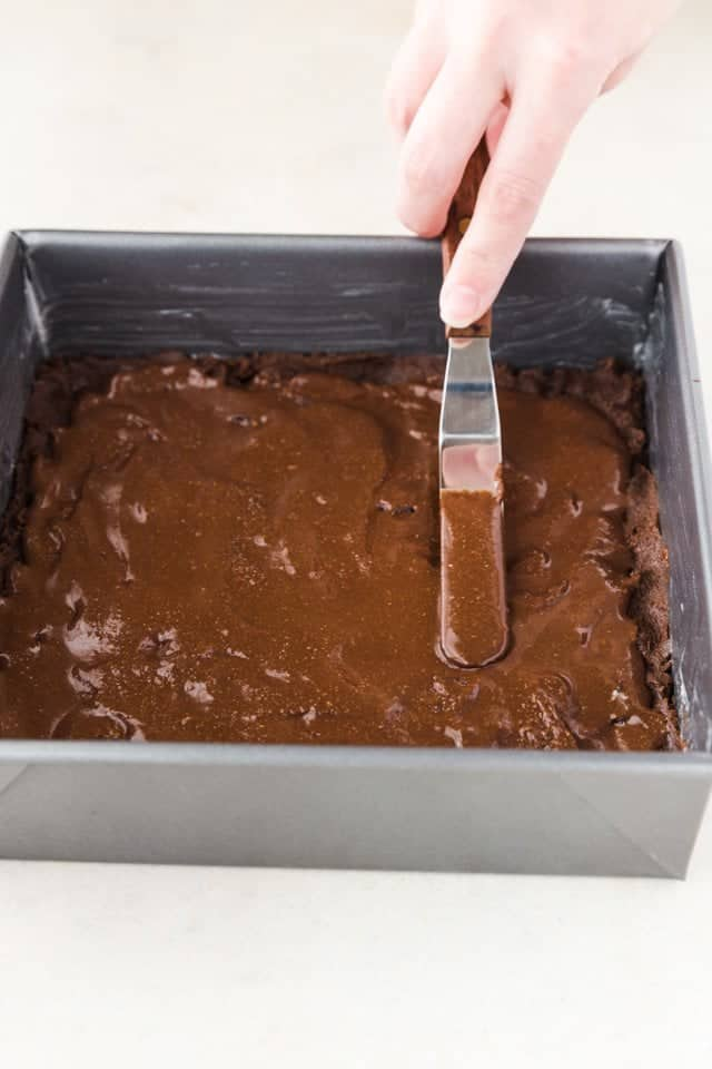 Nutella being spread over chocolate cookie dough in a square baking pan.
