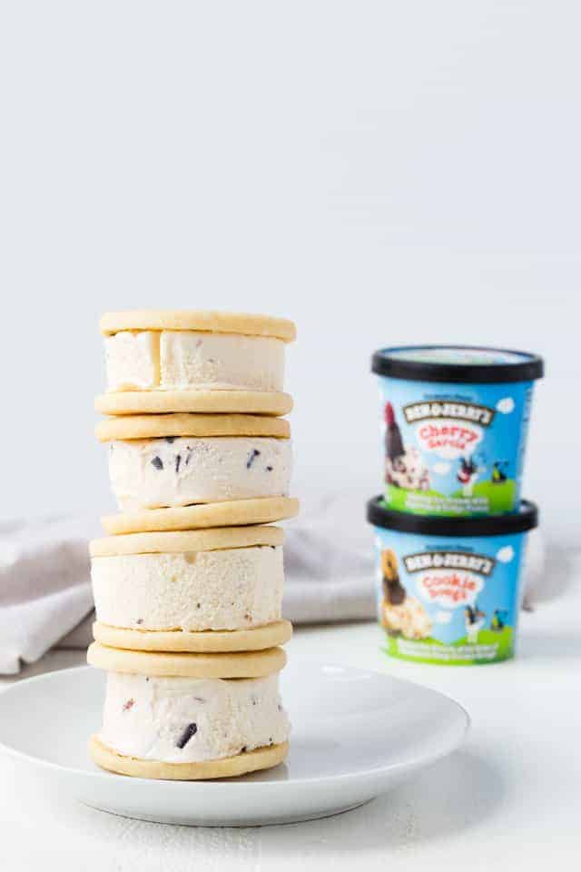 Soft ice cream sandwich cookies stacked four high on a white plate next to cartons of Ben & Jerry's Cups.