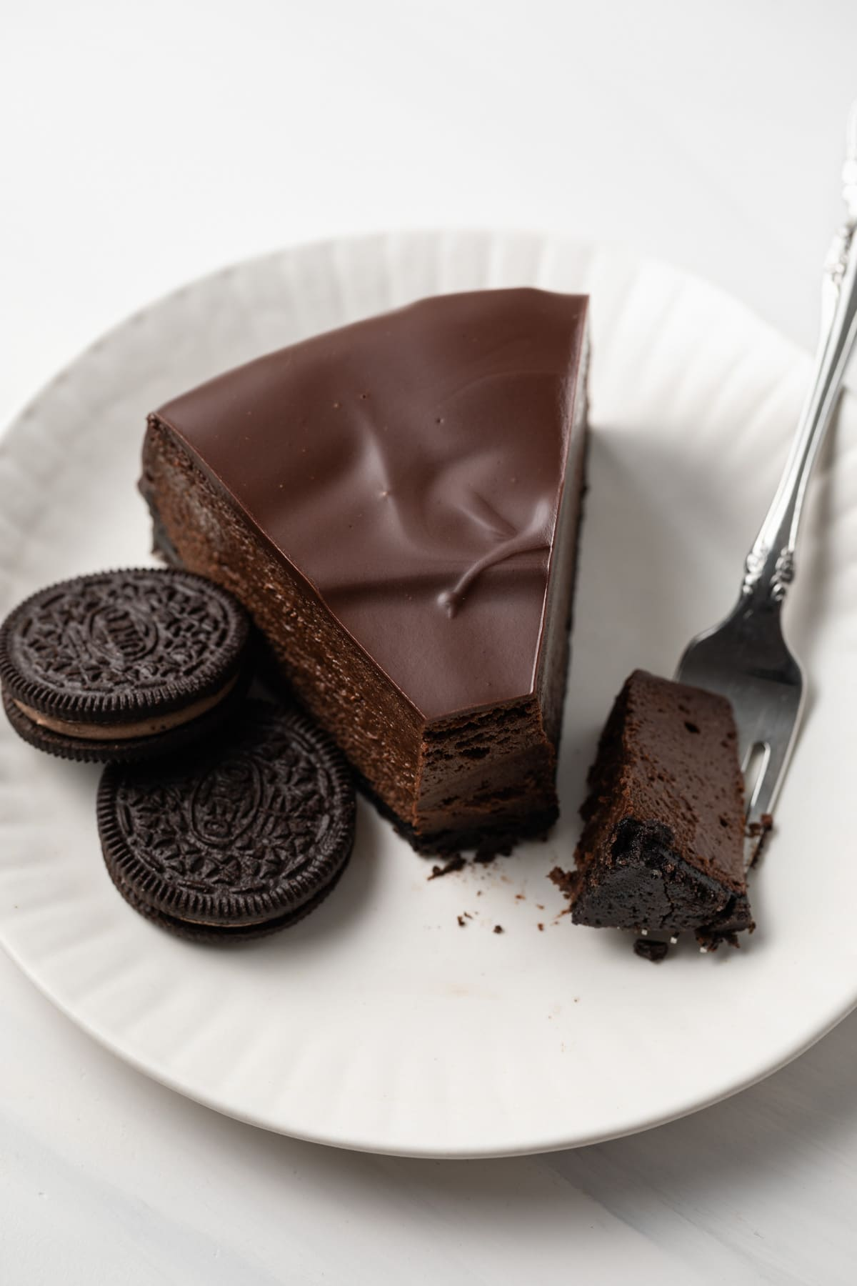 A slice of creamy triple chocolate cheesecake with a fork taking a bite out.