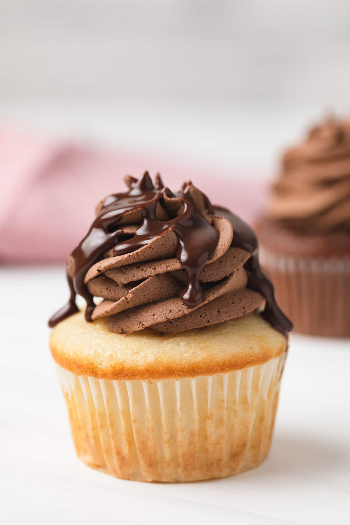 vanilla cupcake topped with chocolate ganache frosting and chocolate glaze