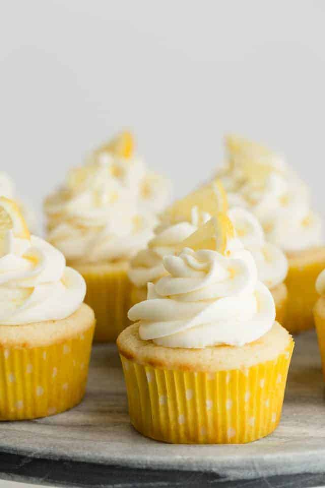 Lemon cupcakes with lemon frosting on a gray marble platter.