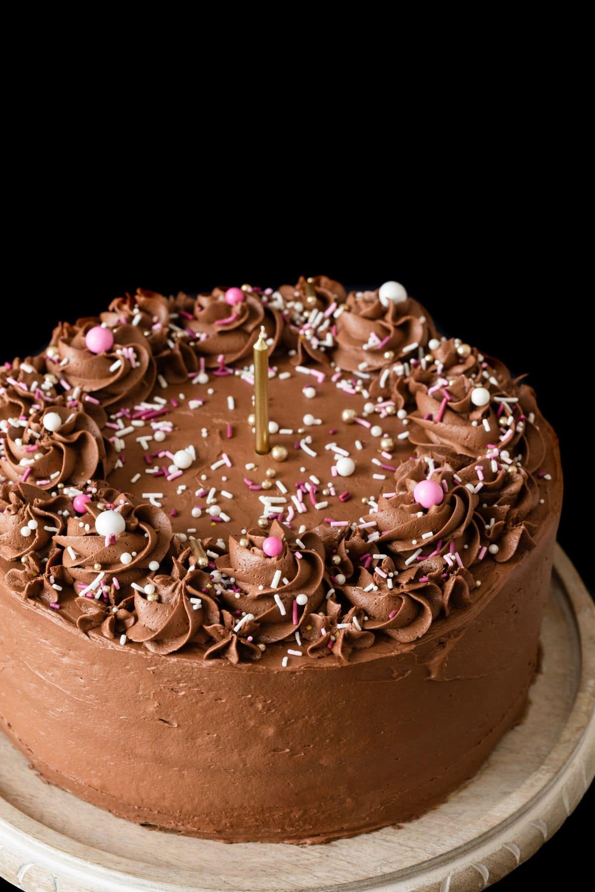 Angled view of homemade birthday cake with chocolate frosting and sprinkles.