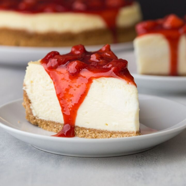 side view of slice of strawberry cheesecake on white plate