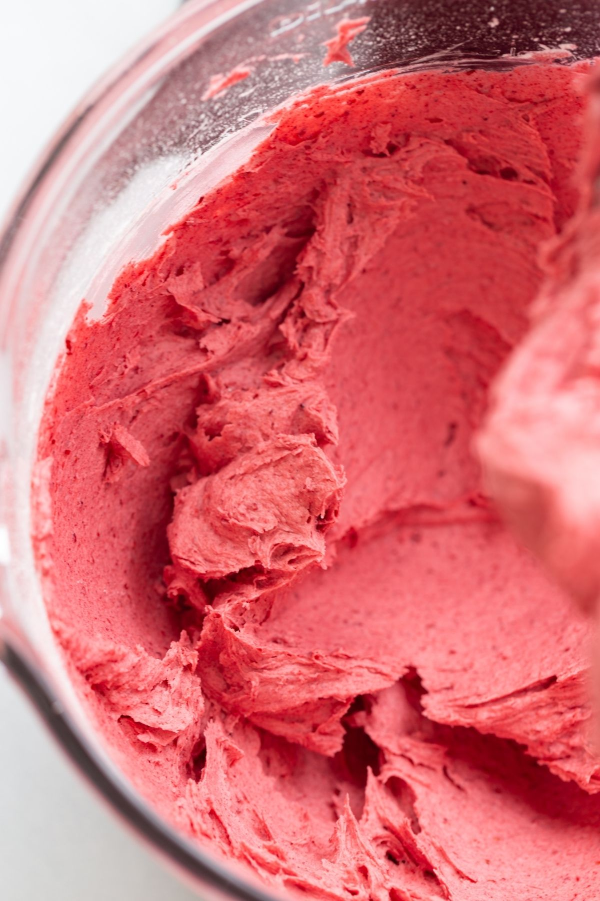angled view of raspberry frosting in a mixing bowl