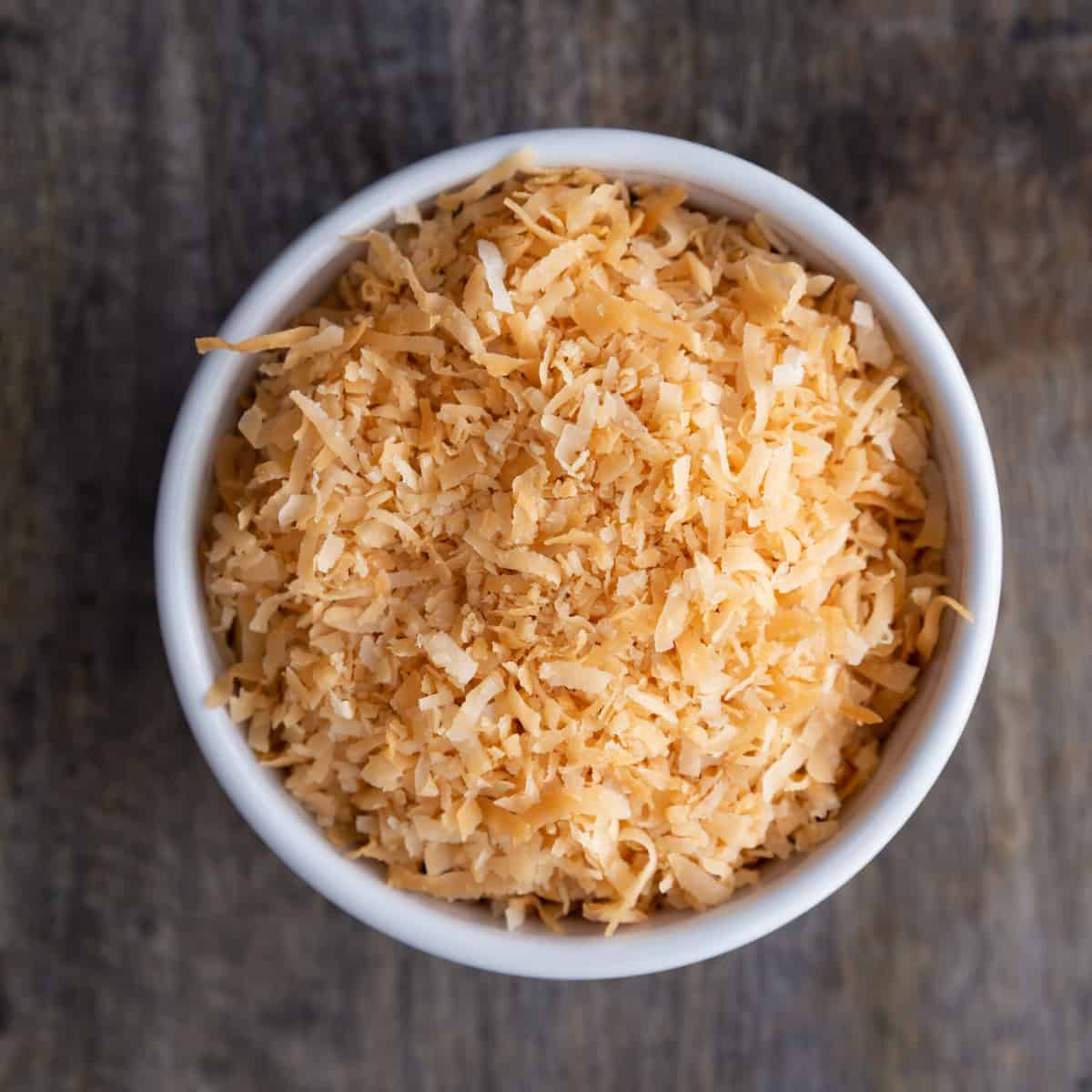 microwave toasted coconut in a white bowl